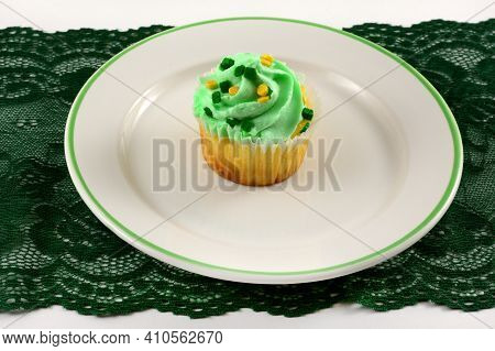 Saint Patrick's Day Cupcake With White Icing On Plate On Green Lace