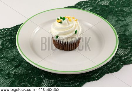 Saint Patrick's Day Brownie Cupcake With White Icing And Sprinkles On White Dessert Plate On Green L