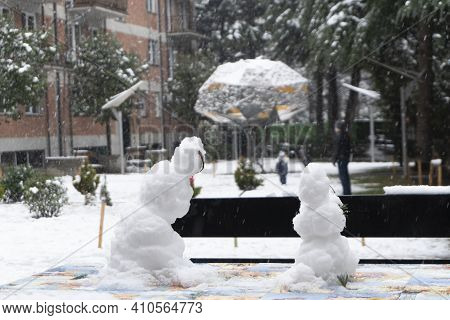 Dad And Son Play On The Playground During A Snowfall. A Pair Of Snowmen In The Foreground. Large Sno