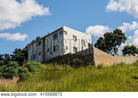 Residential Dwelling Constructe On Top Of Grassy Hill