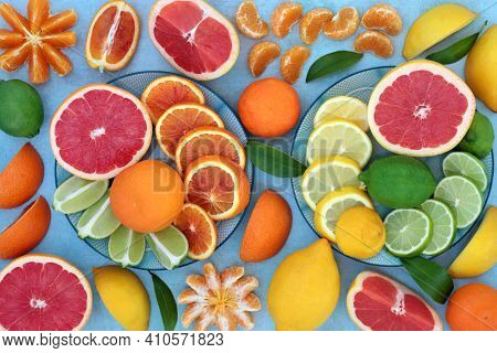 Fresh citrus fruit with oranges, lemons, mandarins, limes and grapefruit high in antioxidants, anthocyanins, lycopene, fibre and vitamin c. Healthy immune boosting concept. On mottled blue.