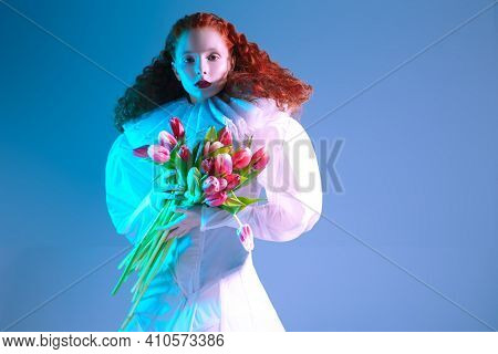 Art portrait of an elegant lady with long red curly hair posing in a white haute couture dress with late renaissance ruffled collar and tulips. Art fashion history.