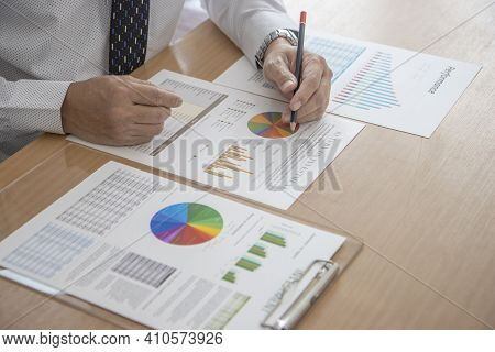 Businessman Is Working In A Modern Office Holding A Pencil While Reviewing Financial Statements And