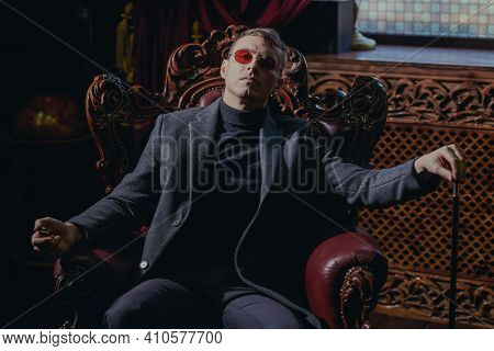 Imperious mature man in stylish expensive clothes and glasses sits in the armchair in the luxury vintage apartment. Gangster man.