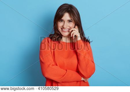 Happy Pleasant Looking Woman With Dark Hair Talking Phone, Hearing Great News, Looks At Camera With