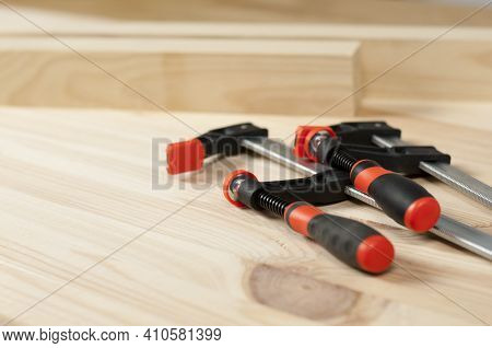 Iron Clamps. Clamps And Vices. Wooden Bars On Workshop Table