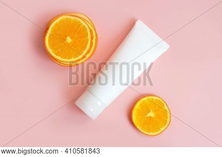 Cream Tube With Vitamin C Branding Concept And Orange Slices On Pink Background. Cosmetic Skincare P