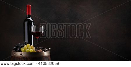 Wine bottle, glass of red wine, grapes and old wooden barrel. With copy space