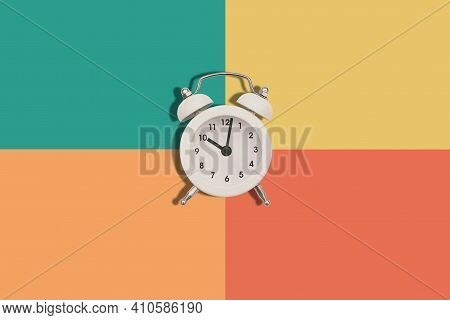 Alarm Clock On A Colored Background. The Hands Of The Clock Show Ten Oclock In The Evening Or In The
