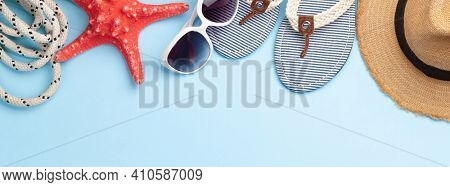 Summer vacation items and accessories. Flip flops, sunglasses and sun hat on blue background. Top view flat lay