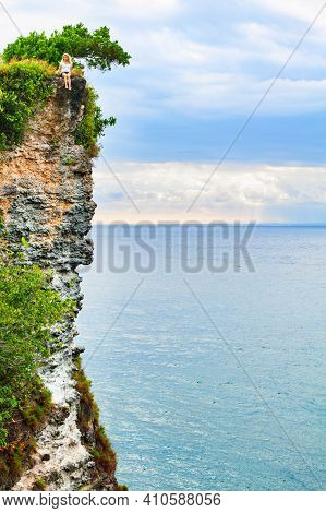 Happy Girl Have Fun On Summer Beach Holiday. Young Woman Relax At Rock Cliff Above Sea. Looking At B