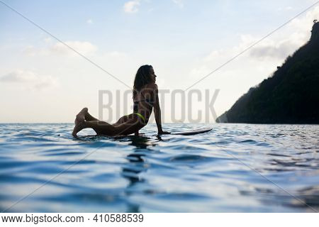 Happy Girl In Bikini Have Fun Before Surfing Surfer Lie On Surf Board, Look At Sunset Sky. People In
