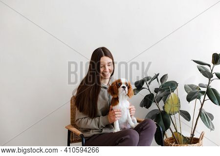 Young Woman With Long Dark Hair Sitting In Rattan Chair With Cavalier King Charles Spaniel Puppy. Wh