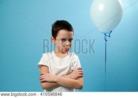Schoolboy Looking At Camera With Crossed Arms Expressing Displeasure