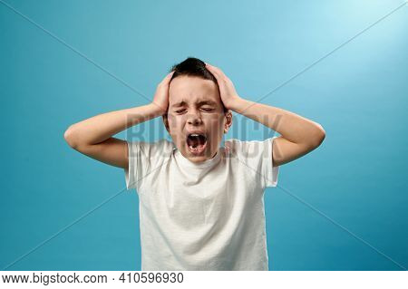 Shocked Boy Screams With His Hands On His Temples, Expressing Shock And Displeasure. Blue Background