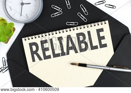Reliable. Text On A Sheet Of Notepad On A Black Envelope On A Light Background