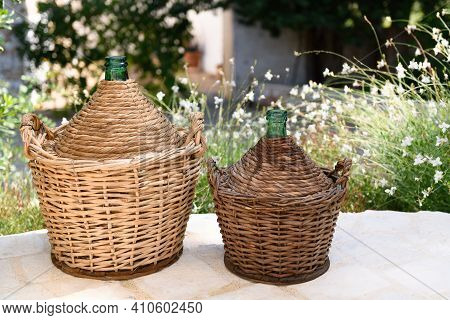 Due Demijohn In A Garden, Made In Puglia Are A Glass Container, Covered With A Wicker Weave In The S