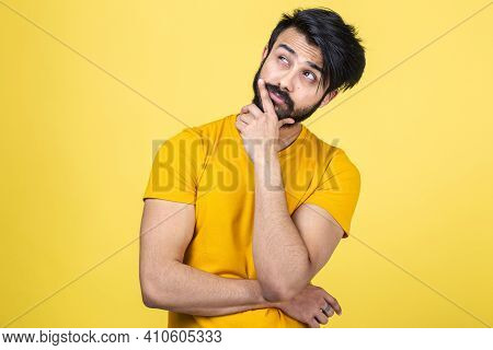 Emotional Portrait Of A Hindu Man In A Yellow T-shirt On A Bright Orange Background