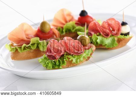 Tender Baguette Canapes With Leaf Lettuce, Salami Or Parma Ham, Tomatoes, Mozzarella And Olive. Deli