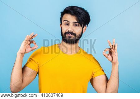 Emotional Portrait Of A Hindu Man In A Yellow T-shirt On A Bright Blue Background