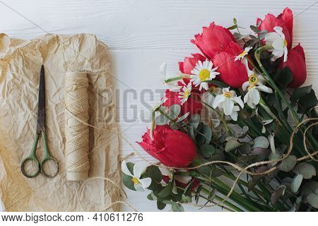 Stylish Red Tulips,daffodils And Eucalyptus Bouquet With Craft Paper, Scissors And Twine On Rustic W