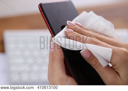 Woman Wiping Screen Of Mobile Phone With Damp Cloth Closeup. Antiseptic During Covid19 Pandemic Conc