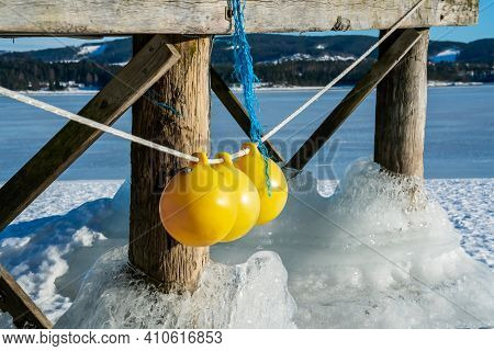 Thick Ice Clinging To The Wooden Pillars Of A Boat Jetty On A Frozen Lake.
