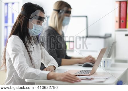 Women Wearing Protective Masks And Shields Working At Computers In Office. Prevention Of Covid19 Con