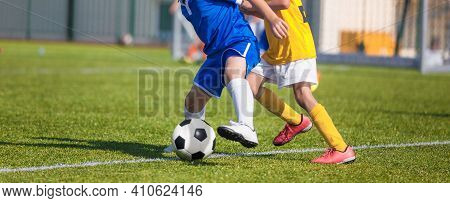 Football Players Compete For A Ball. Children Playing Sports On Grass Pitch. Two Kids In Soccer Duel