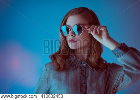 Portrait of a beautiful young woman in elegant glasses on a dark blue background. Glasses fashion.