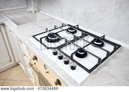 Modern White Gas Stove On Counter Top Closeup. Hob Gas Stove Made Of Tempered White Glass Using Natu