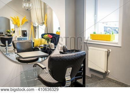 Interior Of A Beauty Salon. Black Leather Chair In Front Of The Mirror In The Beauty Salon. Interior