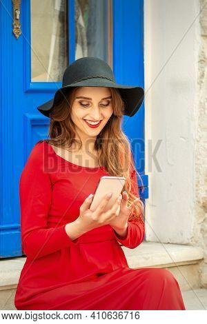 Beautiful Young Caucasian Traveling Woman In Black Hat Looking On The Smartphone Smiling And Sitting