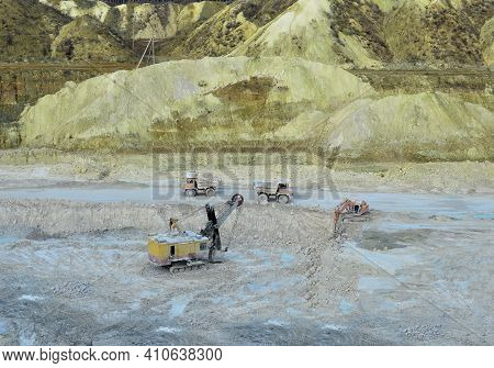 Aerial Top View Of Mining Industry. Excavator In Quarry Loads Rock Into A Mining Truck. Excavators A