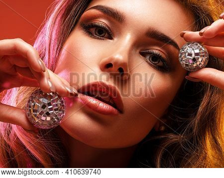 Portrait of beautiful young woman with bright shiny makeup. Blonde with brightly colored long hair. Fashion model holding shiny glass balls. Glamour concept.