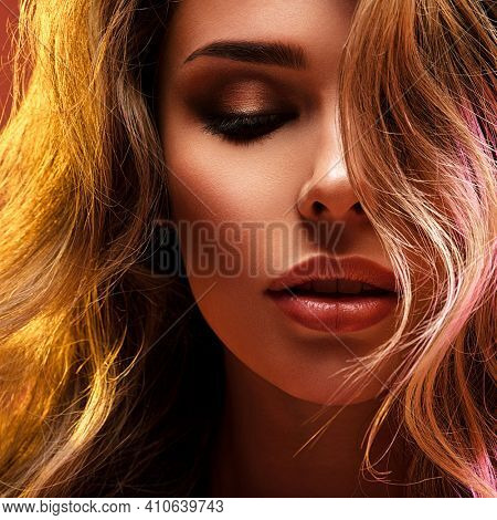 Portrait of beautiful young woman with bright shiny makeup. Blonde with brightly colored long hair. Pretty girl with long curly hair.   Fashion model posing at studio.