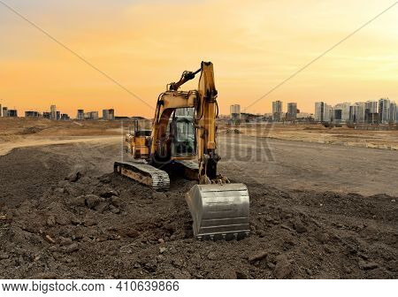 Excavator On Earthworks At Construction Site On Sunset Background. Digging A Foundation Pit And A Tr