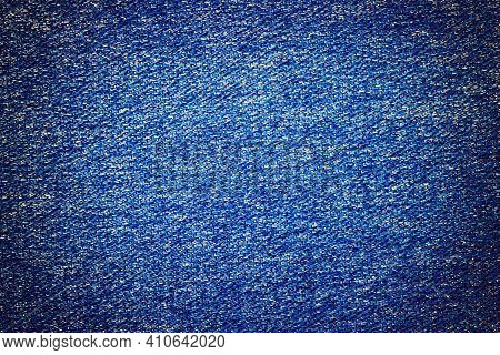Photo Of Blue Textile Material Denim Jeans Texture With Light Coloured Center. Realistic Textural Fa