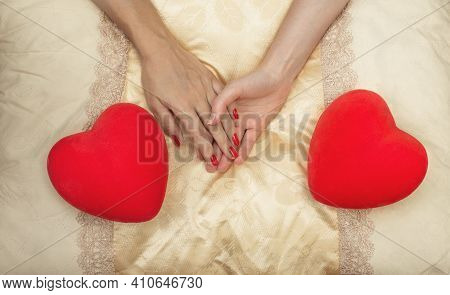 Lgbt Concept. Women Holding Hands On The Bed With Two Hearts