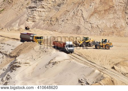 Wheel Loader Loading Sand Into Dump Truck At The Opencast Mining Quarry. Mining Truck Transports San