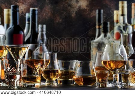Hard Strong Alcoholic Drinks And Distillates In Glasses And Bottles In Assortment: Vodka, Cognac, Te
