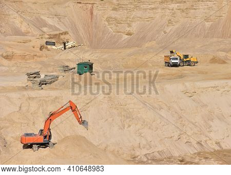Dump Truck Transports Sand In Open Pit Mine. Excavator On The Development Of Sand In A Quarry. Minin