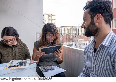 Two Female And A Male Friends Looking At Old Family Photographs Curiously Nostalgia Concept