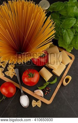 Blurred Image Of Different Types Of Pasta, Tomato, Basil, Seasoning On A Dark Background.photo With