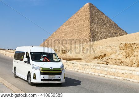 Giza, Egypt - January 26, 2021: Touristic Van Toyota Hiace H300 At The Background Of The Great Pyram
