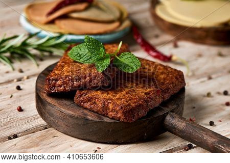 closeup of some tofu fillets on a dark wooden tray on a white rustic table, next to some cold cuts made of tofu and some slices of vegan cheese, in different plates