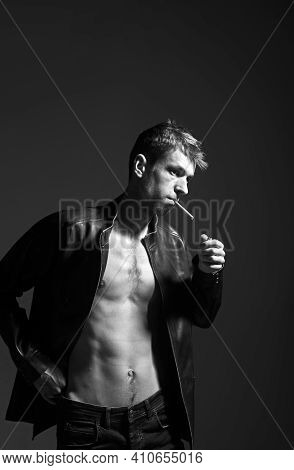 Portrait Of A Rebel Type Guy In Classic Leather Jacket With Cigarette In Mouth Against Dark Backgrou