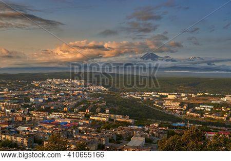 Petropavlovsk-Kamchatsky city at sunset and cone of Koryak volcano. Kamchatka Peninsula, Russia