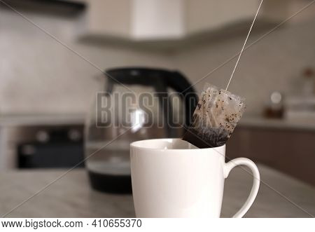 A Used Tea Bag Is Given From A White Mug In The Background Is A Transparent Teapot With A Black Hand