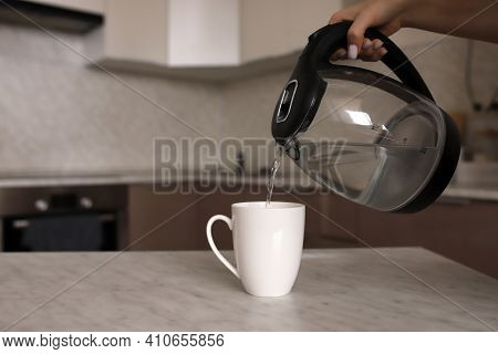 The Girl Makes Tea On The Kitchen Table. A Woman Pours Boiling Water Into A White Mug On The Kitchen